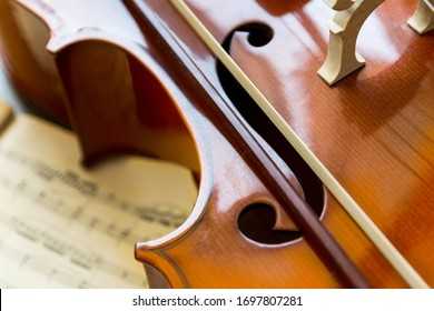 Fragment of a cello on wooden background with music sheets. Rehearsal before the concert. Musical tuition concept.