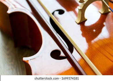Fragment of a cello on wooden background with copy space . Rehearsal before the concert. Musical tuition concept.