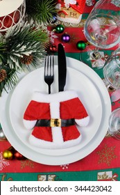 Fragment of the Christmas table serving coat of Santa Claus with cutlery