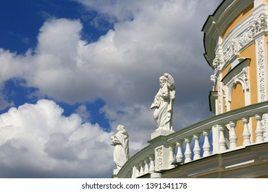 Fragment of the Church of the Nativity of the Blessed Virgin in Podmoklovo, Moscow region, Russia. A rotunda-shaped temple surrounded by statues of the twelve apostles against the sky and clouds