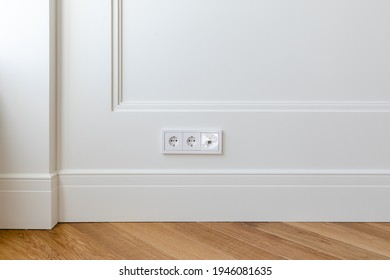 Fragment of classic interior with herringbone parquet floor and panels with installed wall outlet and a network connector. Walls decorated with white moldings and skirting boards.