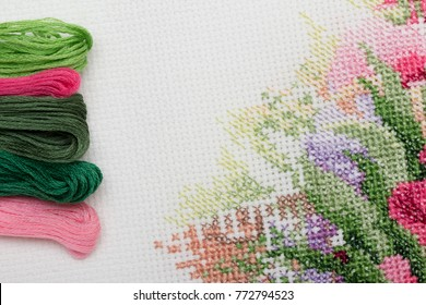 A fragment of colorful cross-stitch embroidered picture with cotton mouline threads. A bunch of colorful cotton embroidery threads on white aida with a fragment of embroidered flowers.