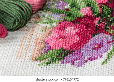 A fragment of a colorful cross-stitch embroidered picture of flowers  on white aida fabric with cotton floss set. Vintage flower embroidery on white aida and colorful cotton embroidery threads.