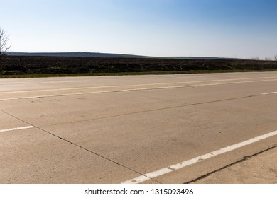Fragment of a concrete road. Close-up of road and blue sky.