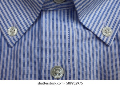 Fragment of cotton shirt close up. Fabric in blue and white stripes with buttons.