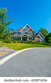 Fragment of custom made luxury house with nicely landscaped and trimmed front yard in the suburbs of Vancouver, Canada.