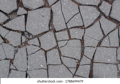 A fragment of damaged, split asphalt road surface consisting of large flat pieces separated by large cracks filled with sand, pebbles, small dry leaves and twigs. Natural cracked  background.