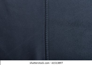 Fragment of a dark-blue leather with a suture.
