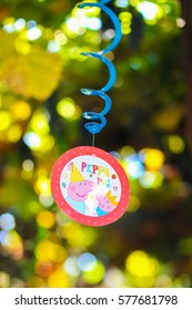 Fragment of decoration, decoration thematic of children's holiday, birthday, photo colorful round medals with image of Peppa pig, suspended on blue spiral and decorated with yellow ribbons, against