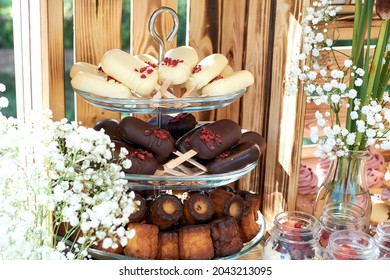 Fragment of a dessert table. cake pops in trouble and dark chocolate and cannele. Gypsophilia in the form of decoration, wooden background.