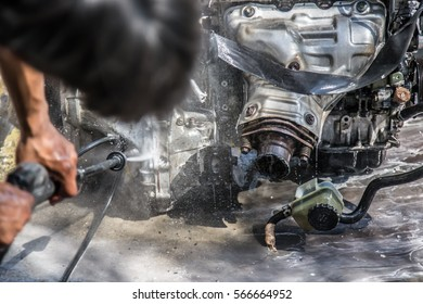 A fragment of the engine car that old and shabby. hand of mechanic is to clean your car's engine safely by water
