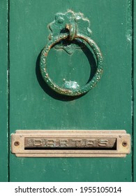 Fragment of an entrance green door with a ring handle and a mailbox.
