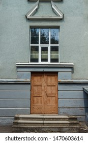 Fragment of the facade beautiful house in neoclassical style. Entrance with window and decors.