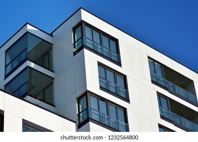 Fragment of a facade of a building with windows and balconies. Modern home with many flats.