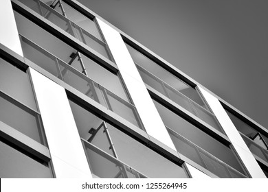 Fragment of a facade of a building with windows and balconies. Modern home with many flats. Black and white.