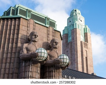 Fragment of facade of Helsinki main railway station with sculptures and clock tower in bright clear winter day, Finland