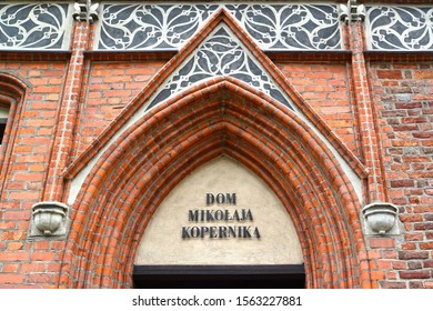 """Fragment of the facade of the old building with the inscription in Polish """"House of Nicholas Copernicus"""" (15th century). Torun, Poland"""