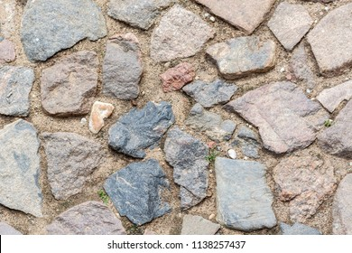 Fragment of the floor of the courtyard of the Mir castle, paved with stone and sand, for use as a background.