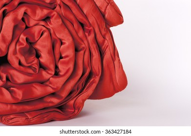 a fragment of folded scarlet blanket, closeup, white isolated