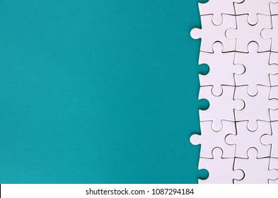 Fragment of a folded white jigsaw puzzle on the background of a blue plastic surface. Texture photo with copy space for text