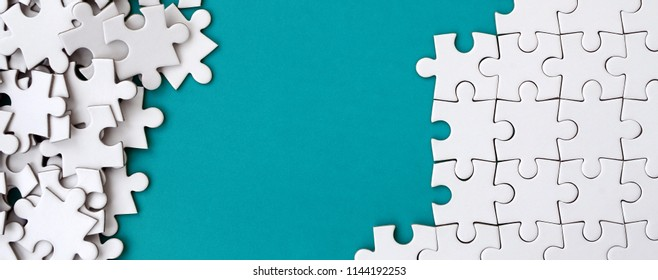 Fragment of a folded white jigsaw puzzle and a pile of uncombed puzzle elements against the background of a blue surface. Texture photo with space for text
