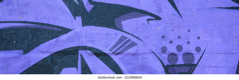 Fragment of graffiti drawings. The old wall decorated with paint stains in the style of street art culture. Colored background texture in purple tones.