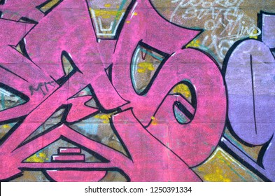 Fragment of graffiti drawings. The old wall decorated with paint stains in the style of street art culture. Colored background texture in purple tones