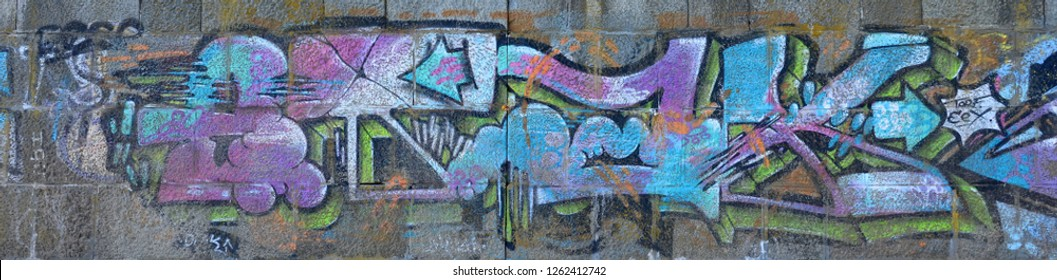Fragment of graffiti drawings. The old wall decorated with paint stains in the style of street art culture. Colored background texture in cold tones