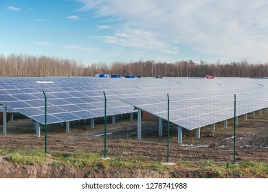 Fragment of ground-mounted solar power station with fixed photovoltaic arrays on a background of sky and trees at late autumn