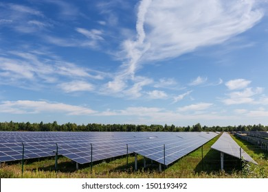 Fragment of the ground-mounted solar power station with fixed photovoltaic arrays on a background of trees and sky with cirrus clouds