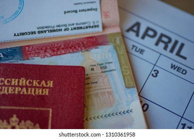 Fragment of H1B visa (for specialty workers) stamp in passport next to  blurred april calendar and red Russian passport on background. H1B visa program deadline concept. Close up view.