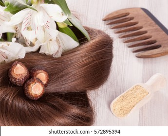 Fragment of healthy shiny woman hair and natural products for haircare; closeup of woman hair, soapnuts, ayurvedic powder, wooden comb and fresh flowers
