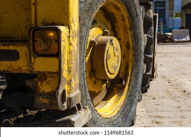 fragment of a heavy worn tractor mounted loader with a huge wheel on a city street during repair work