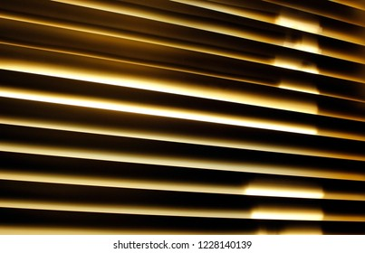 Fragment of high tech blinds / jalousie in office. Strong horizontal lines of laths with golden light shining inbetween. Abstract modern background with dark striped geometry. Urban buisness concept.