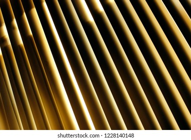 Fragment of high tech blinds / jalousie in office. Strong diagonal lines of laths with golden light shining inbetween. Abstract modern background with dark striped geometry. Urban buisness concept.
