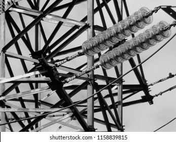 Fragment of high-voltage tower. Power line. Metalware. Black and white photo. BNW. Urban grunge