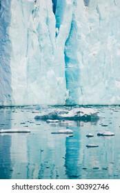 Fragment of iceberg on Spitsbergen island reflecting in water
