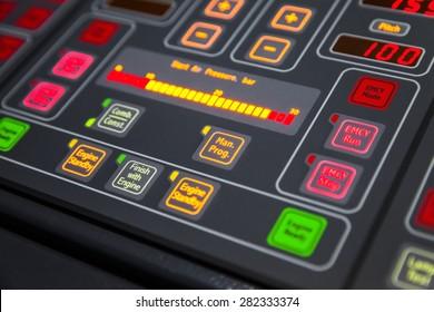 Fragment of illuminated ship control panel on the captain bridge in the dark. Selective focus, shallow DOF