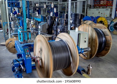 Fragment inside a modern plant producing power electric cables and optical fibers. Interior of modern production line technology obsolescence