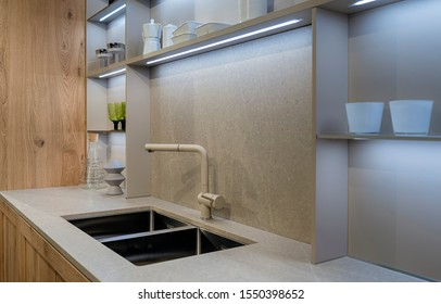 A fragment of the interior of a modern kitchen with a double metal sink and built-in LED lights