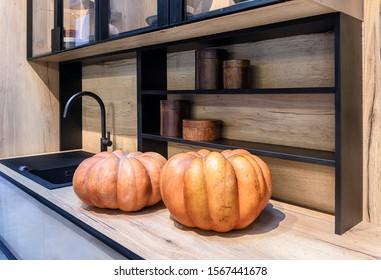 Fragment of the interior of a modern kitchen. Large orange pumpkins lie on a wooden tabletop.