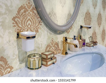 A fragment of the interior of the washroom in a palace style. Marble countertop made of natural stone and gilded faucet
