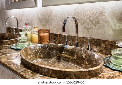 A fragment of the interior of the washroom in a palace style. Marble countertop  and sink made of natural stone