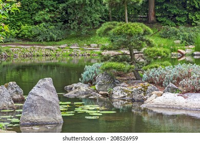 Fragment of a japanese garden with an island, artificially shaped trees and big rocks standing in water