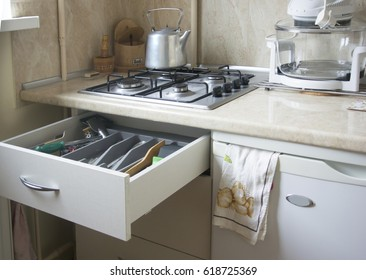 Fragment of kitchen with gas cooker, kettle and drawer with kitchen utensils