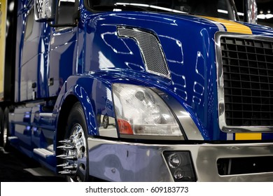 A fragment of a large commercial semi truck with modern design of headlights and a grille, with chrome-plated rims and custom bolt design, a shining bumper and a blue lacquered paint finish with glare