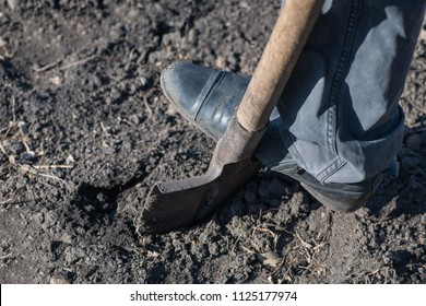 A fragment of a leg of the worker who digs with a shovel empty box with topsoil. Vertical photography