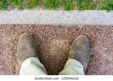 Fragment of legs in light beige trousers and brown shoes against the background of a footpath of small red stone with curb.
