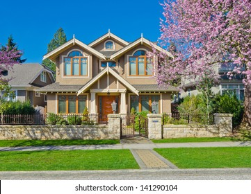 Fragment of the Luxury custom made house behind iron gates with long doorway at sunny day in Vancouver, Canada.