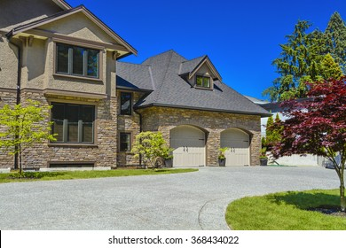 Fragment of luxury house with double garage and concrete driveway in front. Front yard of luxury family house with green lawn and driveway in front on blue sky background